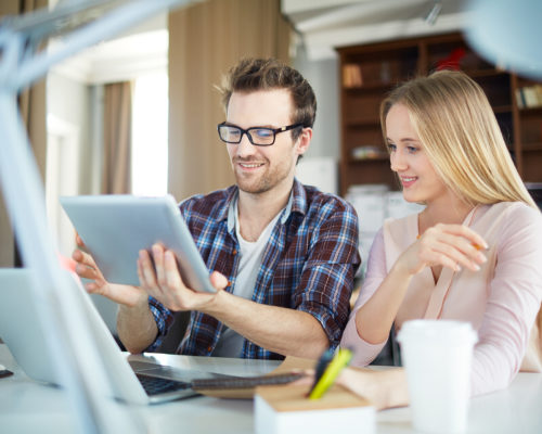 Scene of work process in office: handsome creative man dressed in casual clothes proudly holding up tablet in his hands showing something to blond woman sitting beside him and looking at the screen with curiosity
